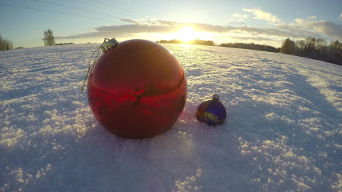 Christmas bauble on snowy december field and sunset light, time lapse 4K Footage