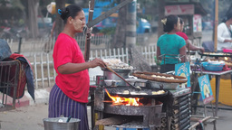 Woman cooking on busy road,Mandalay,Burma Footage