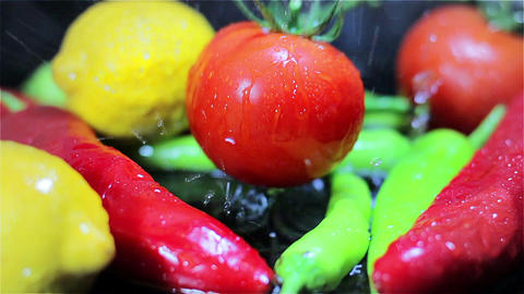 Slowmotion Tomatoes falling into fresh vegetables on black surface Footage