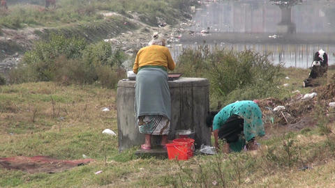 two nepalese woman laundry clothes on sacred polluted river Bagmati coast– Kat Footage