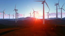 Wind turbine farm over green meadow, rays of light against sunrise, tilt Animation