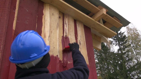 Worker painting house with red paint Footage