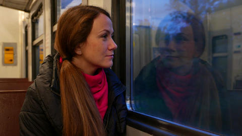 Young adult woman gaze to dark forest through suburban train window, portrait Live Action