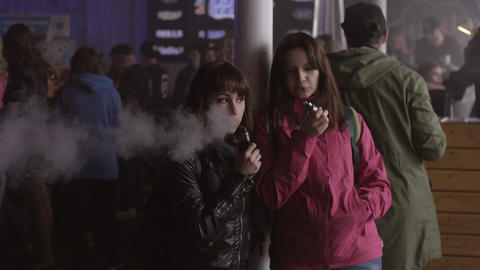 Young girls smoking electronic cigarette on festival. Vapers. Subculture Live Action