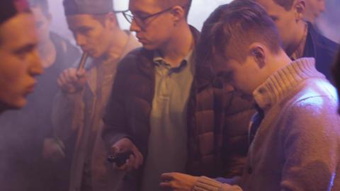 Men smoke electronic cigarette in specialized shop. Vaper. Spotlights. Steam Footage