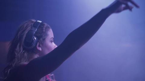 Dj girl in headphones raise hand at turntable in nightclub. Dance. Strobe Footage