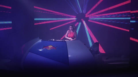 Dj girl in headphones spinning at turntable in nightclub. Holidays. Screen. Spot Footage