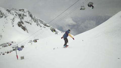 Snowboarder ride down on slope at snowy mountains. Uniform. Ski lifts. Ski resor Footage
