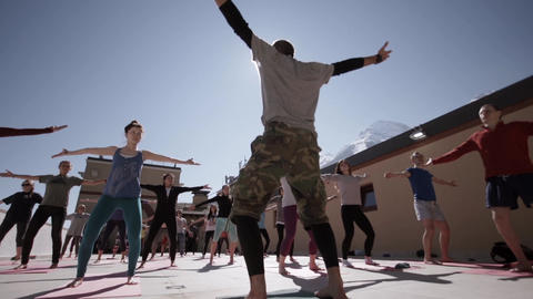 People do yoga at outdoor playground in sunny morning, raise hands. Fresh air. M Footage
