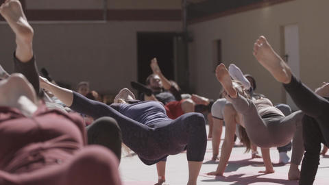 Young people do yoga at open playground in sunny morning, stretching. Fresh air. Live Action