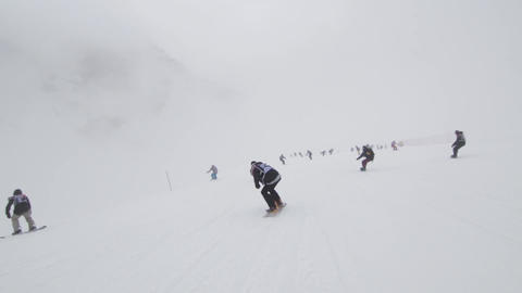 Group of snowboarders riding on snowy slope. Contest. Challenge. Ski resort. Spe Footage