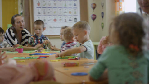 Children Sit at Table and Make Crafts with Nursery-governesses Footage