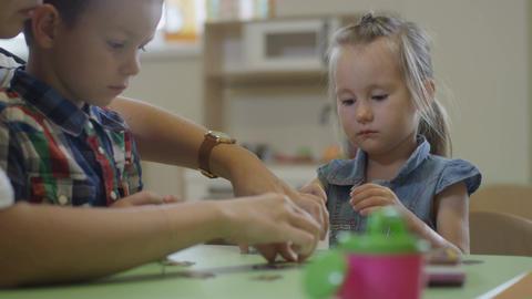 Kind Nursery-governess Helps Boy Glue Paper Detail Footage