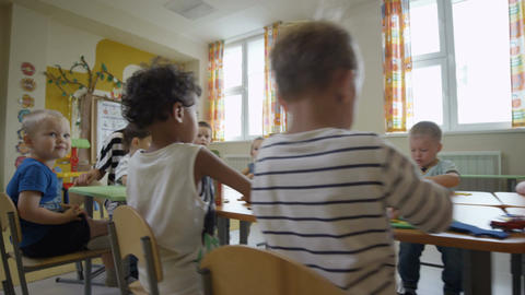 Children Sit at Table with Nursery-governesses in Playroom Footage