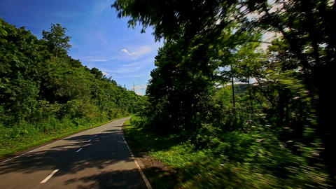 Camera Moves along Country Curvy Road among Hilly Landscape Footage