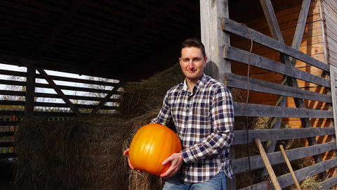 Happy man hold matured pumpkin, stand at hayloft, farmer portrait Footage