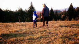 Father and son on a hike, sunset, back view Footage