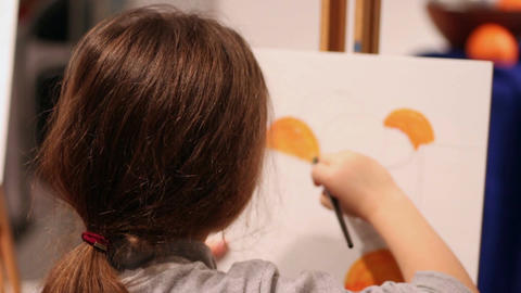 Child painting a picture in orange colours, enjoying the process, art and craft Footage