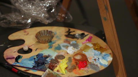 Woman dunking paintbrush in palette with oil paints, art workmanship, hobby Footage