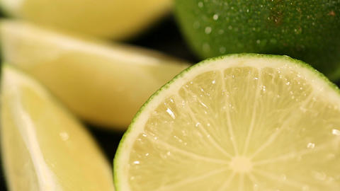 Fresh green lime cut in wedges lying on bar counter for cocktails and beverages Footage