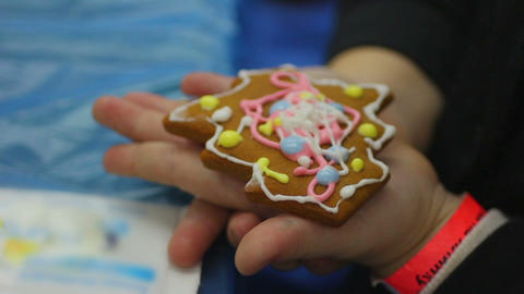 Child hands holding little ginger cookie in the shape of Christmas tree Footage