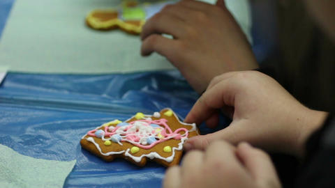 Handmade ginger biscuits, kid decorating Christmas cookies and licking fingers Footage