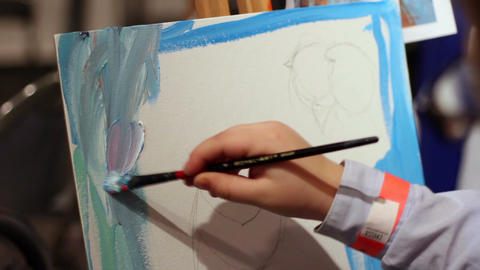 Talented kid painting blue sky on canvas at art school, interesting hobby Footage