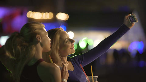Excited blondes posing for selfie at disco, making faces to smartphone camera Footage