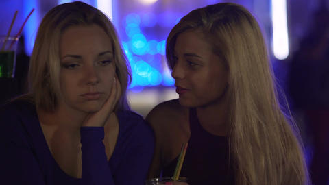 Young woman supporting upset female friend at party, depression after breakup Live Action