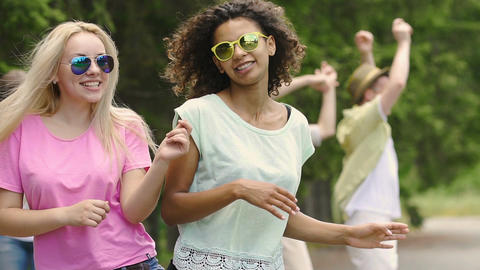 Beautiful young women singing and dancing outdoors, summer holidays, youth Footage