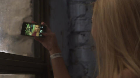 Hot blonde taking selfie for social media, admiring self-portrait on touchscreen Footage