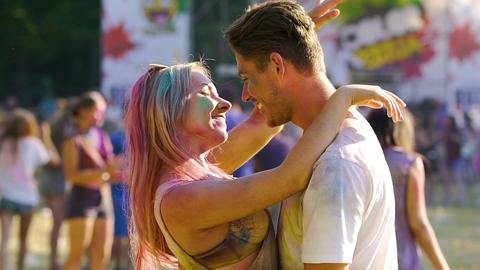 Two young couple dancing and nuzzling at Holi festival, happy people having fun Live Action