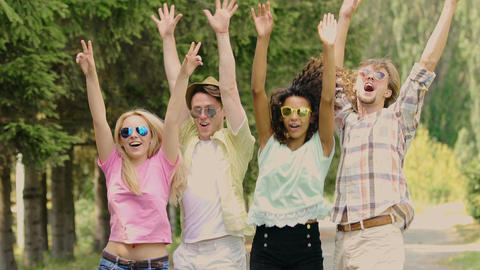 Four young happy people jumping, putting hands in air, dancing at music festival Footage