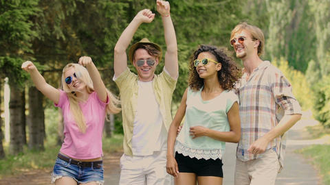 Four young happy people jumping, putting hands in air,…, Live Action