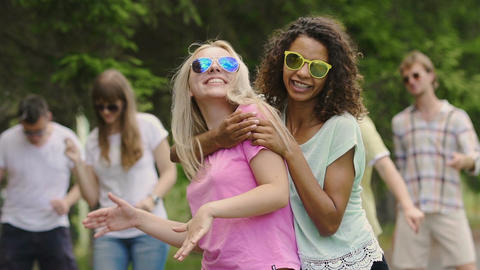 Two multiracial females happily dancing outdoors, young people enjoying party Footage