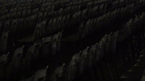 Many rows of old empty chairs in cinema hall, memory of war victims, archives Footage