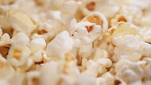 Fluffy popcorn macro, airy popped corn snack served at cinema, entertainment Footage