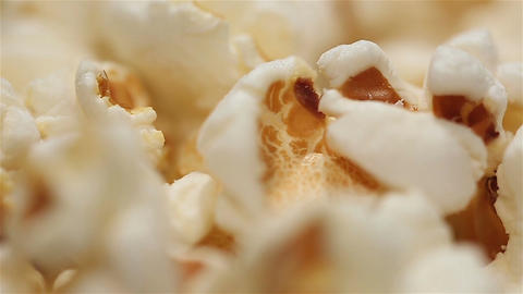 Hot popped popcorn kernels rotating on plate, movie time, high calorie foods Footage