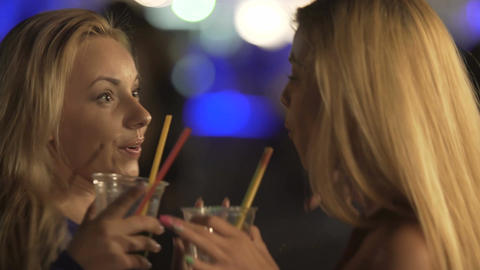 Two beautiful blondes dancing face-to-face with cocktails in hands, flirty girls Footage