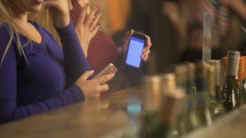 Beautiful women with gadgets in hands, girls having fun, dancing to music at bar Footage