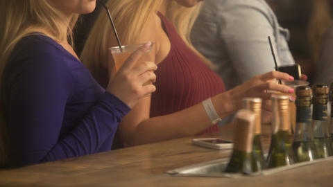 Flirty sexy blondes making seductive moves to music, drinking cocktails at bar Footage