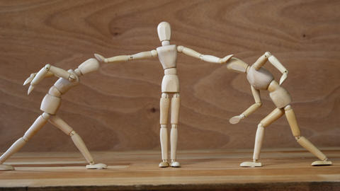 Wooden figurines referee stopping the fight on wooden backgroung Footage