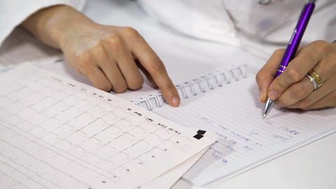 Female doctor Makes a Record of the Results, the Cardiogram Heart Footage