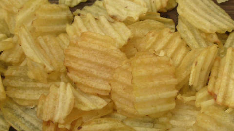 Rippled potato chips on a wooden background Live Action