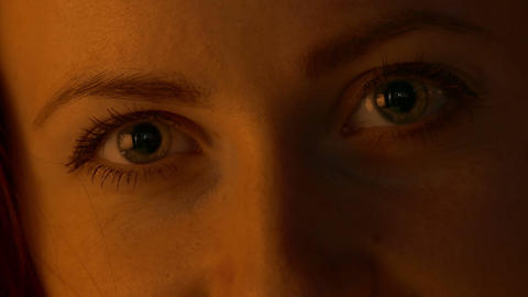 1080p Young Woman Eyes Close-Up Under Warm Low-Key Lighting Footage