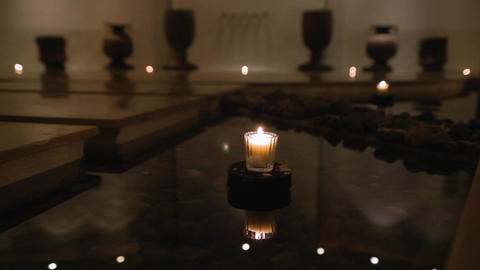 Small white candle on pedestal in shallow pool Footage