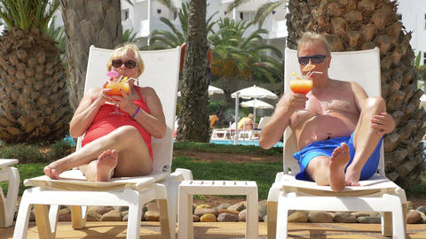 Video of senior couple drinking cocktails on the sunbeds in 4K Footage