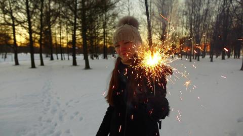 Girl enjoy burning sparkler stick, stay at dusk winter park, show to camera Live Action