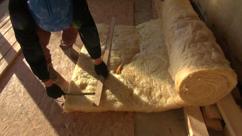 Builder measuring and cutting mineral wool Live Action