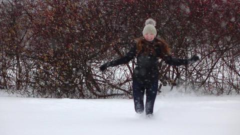 Cheerful girl run towards camera in blizzard through fluffy snow field Footage